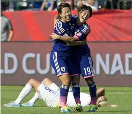 Japan's Azusa Iwashimizu and Saori Ariyoshi (19) celebrate the team's 2-1 win as England's Steph Houghton lies on the ground after a semifinal in the FIFA Women's World Cup soccer tournament, Wednesday, July 1, 2015, in Edmonton, Alberta, Canada. (Jason Franson/The Canadian Press via AP)