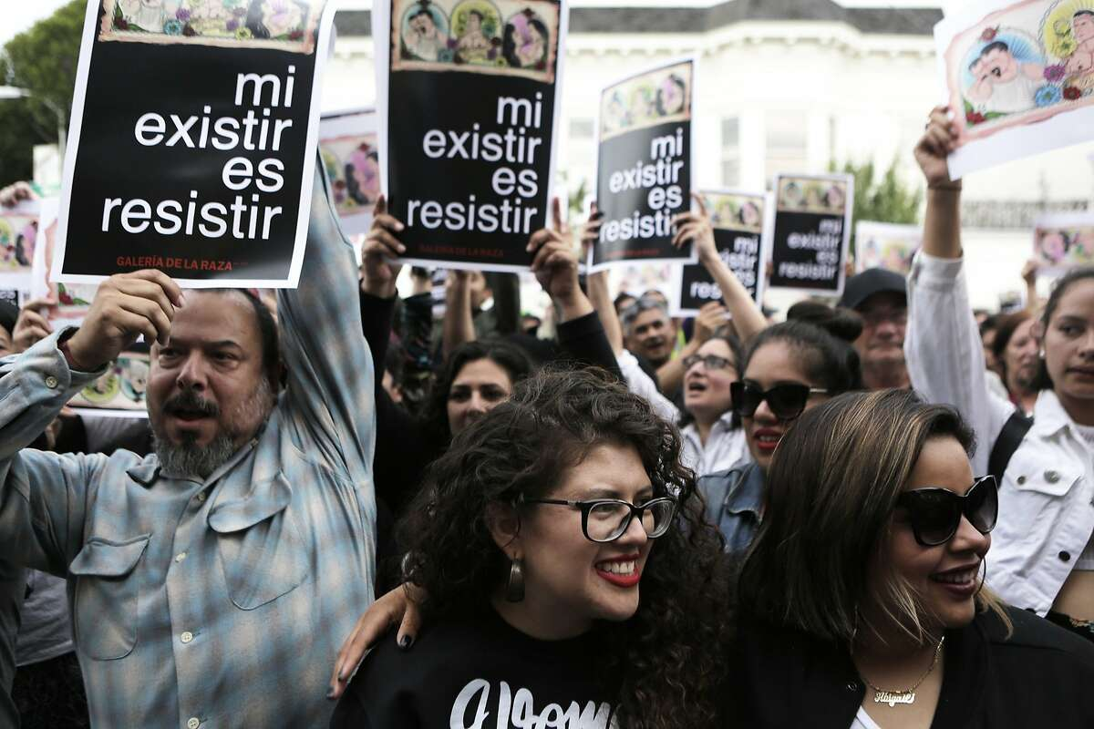 Attendees hold up their signs and cheer in support during a rally on Wednesday, July 1, 2015 at the mural in the Mission District in San Francisco, Ca.. The mural at the Galeria de la Raza is in celebration of the LGBT and Latino culture in the Mission District.