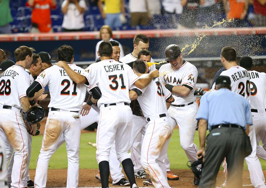Justin Bour (third from right) is mobbed by Miami teammates after his game-winning, three-run homer in the ninth. Photo: David Santiago, McClatchy-Tribune News Service