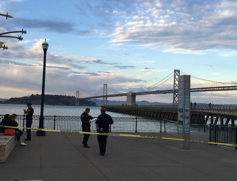 Police investigators at Pier 14 on San Francisco's Embarcadero about 90 minutes after a woman was shot on the long narrow pedestrian pier. The people sitting on the left are passers-by who were on the scene when the fatal shooting occurred. Photo: John King, The Chronicle