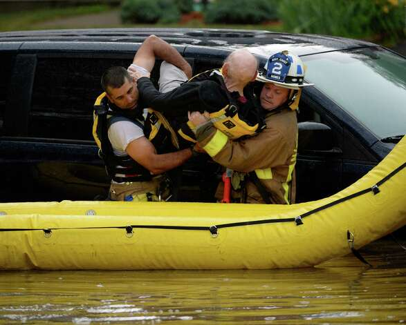 Niskayuna firefighters remove the first of two people from a flooded vehicle Wednesday afternoon, July 2, 2014, on Merlin Drive after heavy rains hit Niskayuna, N.Y. A furious afternoon storm flooded roads, tore down trees, knocked out power to thousands and stranded motorists across the Capital Region. (Skip Dickstein / Times Union) Photo: SKIP DICKSTEIN
