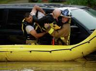 Niskayuna firefighters remove the first of two people from a flooded vehicle Wednesday afternoon, July 2, 2014, on Merlin Drive after heavy rains hit Niskayuna, N.Y. A furious afternoon storm flooded roads, tore down trees, knocked out power to thousands and stranded motorists across the Capital Region. (Skip Dickstein / Times Union)