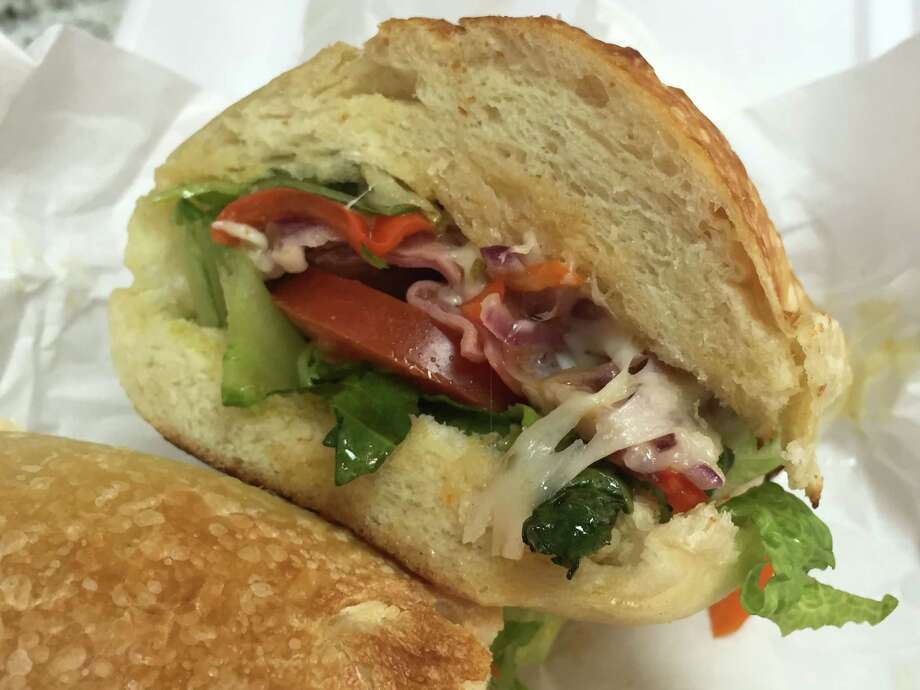The Italian sub at Capos Pizza includes Italian ham, Genoa salami, capicolla, provolone, romaine, Roma tomatoes, onions, banana peppers and Italian vinaigrette on a house-made roll. Photo: Edmund Tijerina /San Antonio Express-News