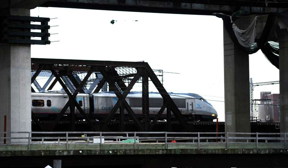 A Metro-North train passes over the Housatonic River on the Devon Railroad Bridge Tuesday, Jan. 20,