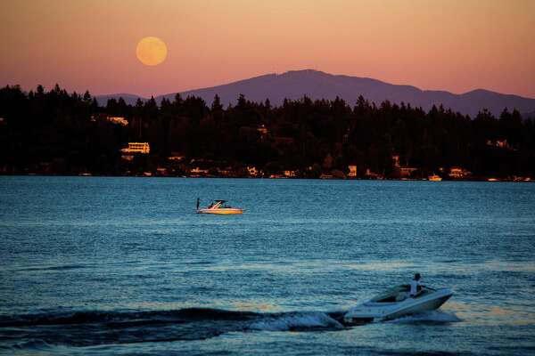 A full moon rises Wednesday, July 1, 2015, as seen from Madison Park in Seattle, Washington.