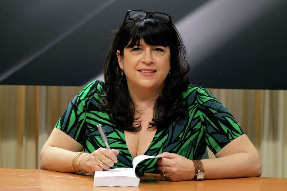 "British author E.L. James poses before she signs a copy of her new book ""Grey: Fifty Shades of Grey as Told by Christian"" for a fan at the Barnes and Noble store on Fifth Avenue in New York on June 18, 2015. The ""Fifty Shades"" trilogy is a record-breaking contemporary publishing phenomenon, selling more than 125 million copies worldwide and translated into more than 50 languages. AFP PHOTO/JEWEL SAMADJEWEL SAMAD/AFP/Getty Images Photo: JEWEL SAMAD, Staff / AFP"