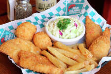 """Sea Island Shrimp House presents its """"Crispy Catch"""" platter that features two white fish fillets and two stuffed shrimp, quick-fried in crunchy panko crumbs and paired with french fries, homemade coleslaw, and two hushpuppies."""