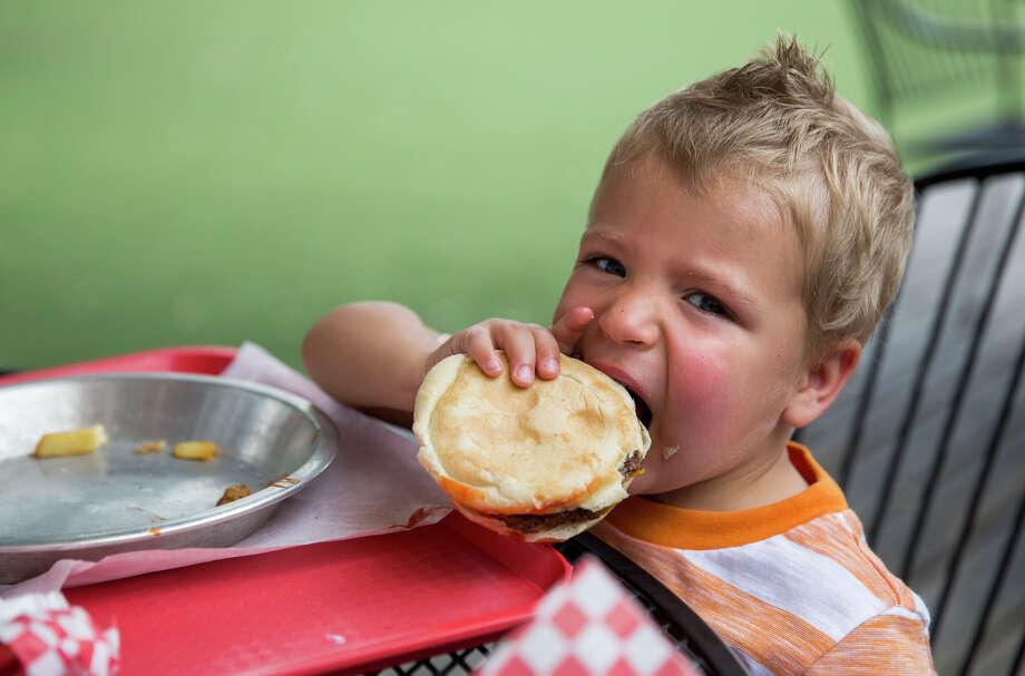 Kai Burton, 2, eats a cheeseburger at Big'z Burger Joint. Photo: Carolyn Van Houten /San Antonio Express-News / 2015 San Antonio Express-News