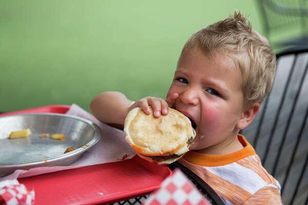 Kai Burton, 2, eats a cheeseburger at Big'z Burger Joint.