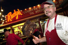 Bob Phariss, manager at Rudy's Country Store and Bar-B-Q holds a brisket just off the pit in front of the popular barbeque eatery in 2000.