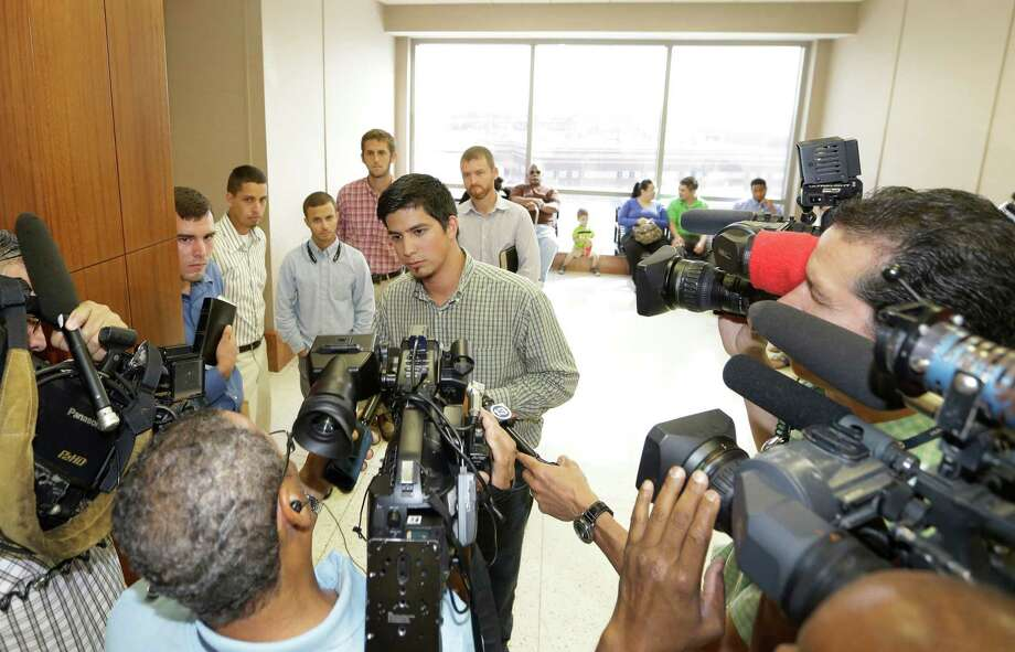 "Jacob ""Jake"" Gardner, front right, speaks to the media as he and Mark DeRouville, left, Randall Valdez, Matthew Martinez, Kevin Fessler, and Richard Trudeau, back right, all members of the Church of Wells in East Texas, wait to be arraigned at Harris County Criminal Courthouse, 1201 Franklin Criminal Court,  Thursday, July 2, 2015, in Houston. They have been charged with criminal trespass after allegedly disrupting Sunday morning services at Lakewood Church. Photo: Melissa Phillip, Houston Chronicle / © 2015  Houston Chronicle"