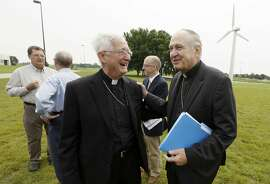 Bishop Richard Pates of the Diocese of Des Moines, right, talks with Bishop Martin Amos of the Diocese of Davenport, following a news conference, Thursday, July 2, 2015, in Ankeny, Iowa. Roman Catholic leaders in Iowa are calling for presidential candidates to focus on the environment and income inequality in 2016.