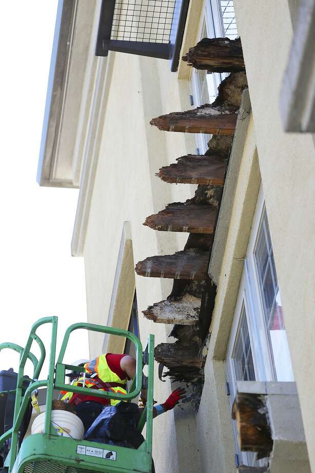 Workers looking at the broken joists of a  fourth story balcony that collapsed and killed six Irish students onTuesday, at the Library Gardens Apartments in downtown Berkeley, Calif., June 18, 2015. Two independent engineers have said they had seen what they considered clear evidence that the balcony that fell in Berkeley was ridden with dry rot and decay. (Jim Wilson/The New York Times) Photo: Jim Wilson, New York Times