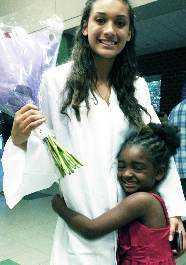 The ceremony over, it's time to celebrate with loved ones following the New Milford adult education commencement exercises, June 10, 2015 at New Milford High School. Above, niece Renee Cruz, 5, offers her congratulations to proud graduate Ivelisse Logue in the every best way she knows how. Photo: Norm Cummings / Norm Cummings / The News-Times