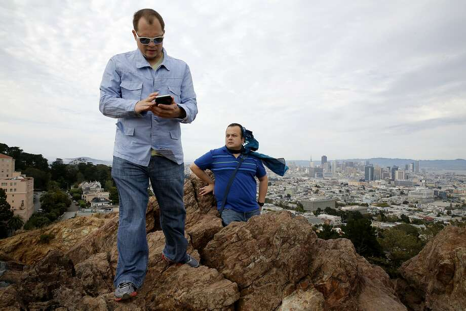 Leo Ivanov (left) uses his cell phone as Roman Baltodano takes in the view from Corona Heights Park in San Francisco, California, on Wednesday, July 1, 2015. Google Maps Street View and the San Francisco Recreation and Park department launched an image-mapping project of some Bay Area parks and trails on June 30. The application allows users to see 360-degree images of the park and get trailhead directions. Photo: Connor Radnovich, The Chronicle