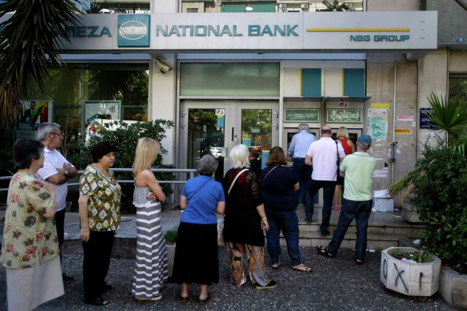 """People stand in a queue to use an ATM outside a closed bank, next to a sign on the plant, bottom right, reading """"NO"""" in Athens this week. Greece is mired in debt, and Europe's attempt to acvhieve lovey-dovey political harmony through economic unity led to neither. Photo: Thanassis Stavrakis /Associated Press / AP"""
