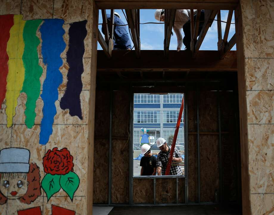 "Students Rivandy Junus (top left), Kelly Li (top right), Adrian Andrade (bottom left) and David Jarillo (bottom right) work on the construction of a tiny house during the ""building and construction trades lab"" at O'connell High School in San Francisco, California, on Thursday, July 2, 2015. The course is taught by Chris Wood. Photo: Loren Elliott, The Chronicle"