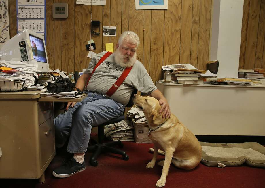 "Tim Crews the editor and publisher of the Sacramento Valley Mirror with his dog ""Tara"" in the newsroom of their operation in downtown Willows, Calif., on Thurs. July 2, 2015. Photo: Michael Macor"