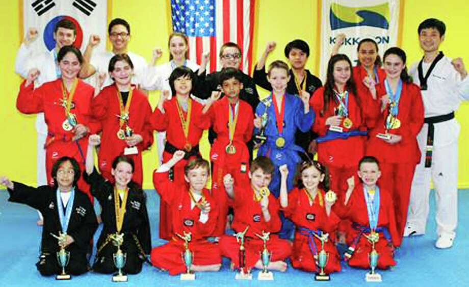 Martial artists from Hong's Taekwondo Academy of New Milford pose proudly with medals and trophies earned in a recent national competiton. Photo: Contributed Photo / The News-Times Contributed