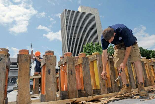 Ryan Drew, right, of Santore's World Famous Fireworks puts together platforms in preparation for the Price Chopper presented New York State's Fourth of July Celebration at the Empire State Plaza on Thursday, July 2, 2015, in Albany, N.Y.  (Michael P. Farrell/Times Union) Photo: Michael P. Farrell / 00032474A