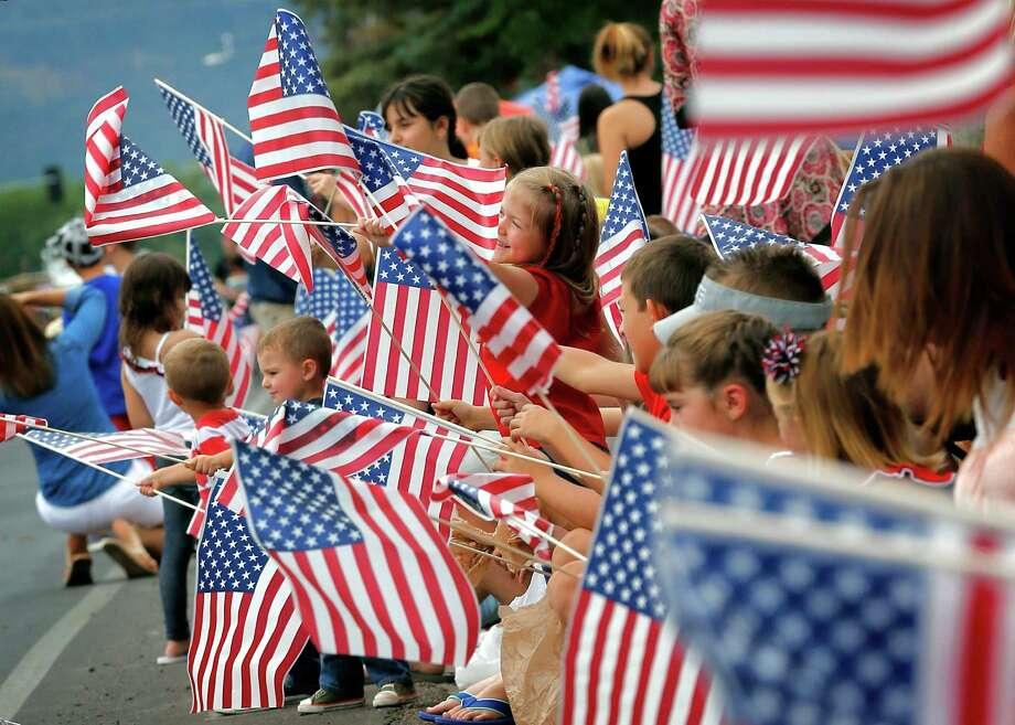 Our flag waving tends to take on a political spin these days. People wave flags as the Independence Day parade rolls down Main Street in Eagar, Arizona last year. Photo: Matt York /Associated Press / AP