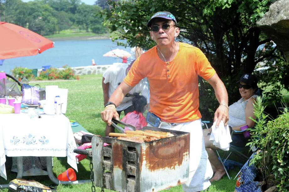 Johnny Rosero makes a barbeque for the family enjoying the holiday at Byram Park in Byram, Conn., Thursday, July 4, 2013. According to the National Retail Federation 65 percent of Americans will stay home this year to barbecue with their family for the holiday weekend. Chamber of Commerce Director Marcia O'Kane said that statistic may be a little high for Greenwich, where many residents leave town for the weekend. Photo: Helen Neafsey / Helen Neafsey / Greenwich Time