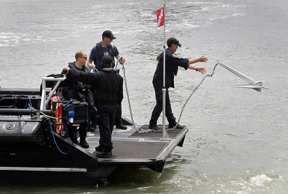 A police department dive team drops anchor before searching for evidence off of Pier 14 in San Francisco, Calif. on Thursday, July 2, 2015 after a woman was shot and killed walking on the pier with her father yesterday afternoon. Photo: Paul Chinn, The Chronicle