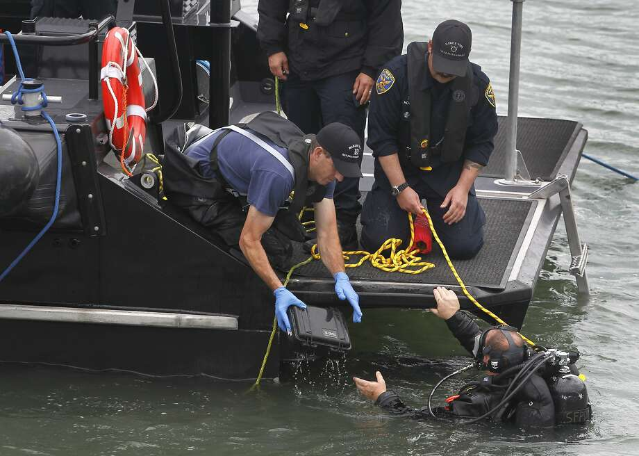 A police department diver hands a box possibly containing evidence found in the bay near Pier 14 to another officer in San Francisco, Calif. on Thursday, July 2, 2015 after a woman was shot and killed walking on the pier with her father yesterday afternoon. Photo: Paul Chinn, The Chronicle