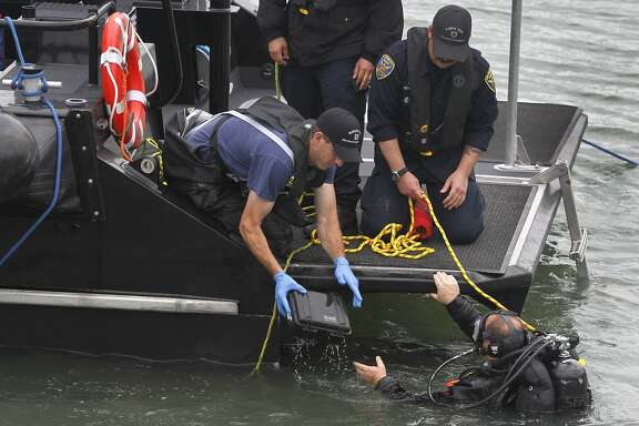 A police department diver hands a box possibly containing evidence found in the bay near Pier 14 to another officer in San Francisco, Calif. on Thursday, July 2, 2015 after a woman was shot and killed walking on the pier with her father yesterday afternoon.