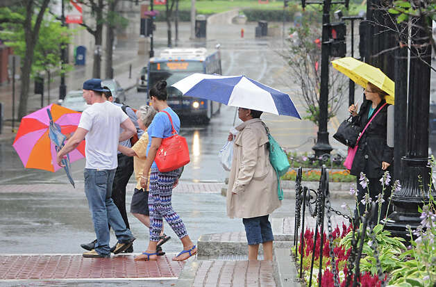A couple of men help a woman, who apparently fell, cross State St. in the rain on Wednesday, July 1, 2015 in Albany, N.Y. (Lori Van Buren / Times Union) Photo: Lori Van Buren, Albany Times Union