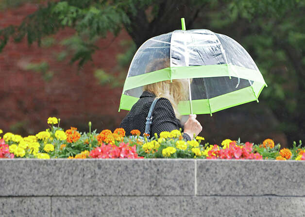 A woman leaves an office building on Washington Ave. in the rain on Wednesday, July 1, 2015 in Albany, N.Y. (Lori Van Buren / Times Union) Photo: Lori Van Buren, Albany Times Union