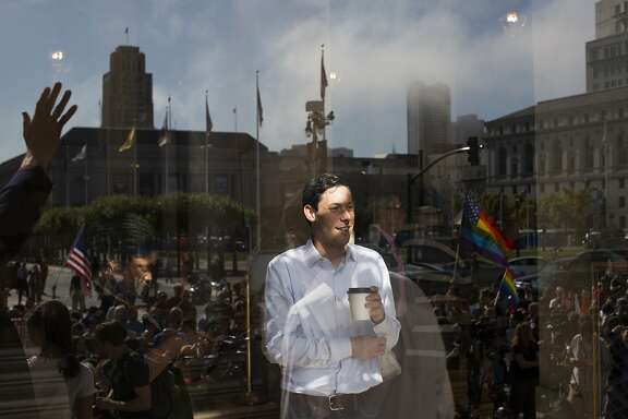 Matthew Podolin takes a break from work to watch people gather at the steps of City Hall in San Francisco, Calif. on Friday, June 26, 2015, celebrating the United States Supreme Court's ruling that gays and lesbians have the constitutional right to marry nationwide.