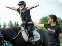 Alicia Crossley, 15, extends her arms during a riding session Monday, June 29, part of an exercise that aides in balance and core strength at Little Britches Therapeutic Riding in Roxbury. Alicia, who has been riding at Little Brtiches for eight years, has Down's syndrome.