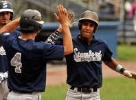 Stamford's Luke Dawson, left, high-fives team mate Randy Polonia after Polonia scored on an inside-the-park home run during their Senior American Legion baseball game against Wilton at Cubeta Stadium in Scalzi Park in Stamford, Conn., on Thursday, July 2, 2015.