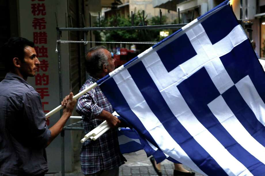 A man sells Greek flags in the street in central Athens, Friday, June 26, 2015. The bitter standoff between Greece and its international creditors was extended into the weekend, just days before Athens has to meet a crucial debt deadline which could decide whether it goes bankrupt and gets kicked out of the euro currency club. (AP Photo/Petros Karadjias) Photo: Petros Karadjias, STF / AP