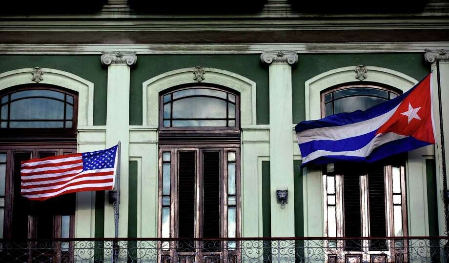 In this Jan. 19, 2015 file photo, a Cuban and American flag wave from the balcony of the Hotel Saratoga in Havana. President Barack Obama will announce July 1 that the U.S. and Cuba have reached an agreement to open embassies in Havana and Washington, a senior administration official said.  (AP Photo/Ramon Espinosa, File) Photo: Ramon Espinosa, STF / AP
