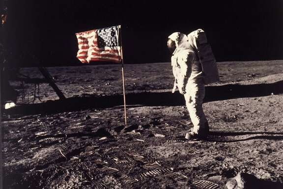 """In this July 20, 1969 file photo, astronaut Edwin E. """"Buzz"""" Aldrin Jr. stands next to a U.S. flag planted on the moon during the Apollo 11 mission. Aldrin and Neil Armstrong were the first men to walk on the lunar surface. (Neil A. Armstrong/NASA via AP)"""