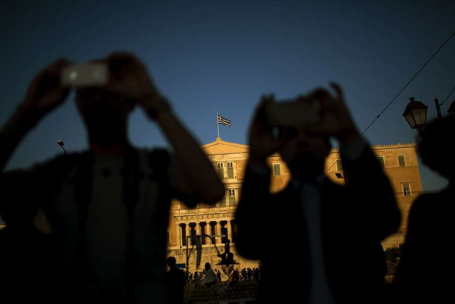 People take photos as demonstrators from the Greek Communist party gather during a rally supporting the no vote for the upcoming referendum in front of the parliament in Athens, Thursday, July 2, 2015. The battle for Greek votes entered full swing Thursday ahead of a crucial weekend referendum that could decide whether the country falls out of the euro. Photo: Emilio Morenatti, Associated Press