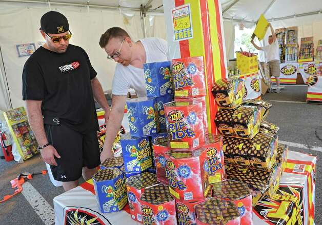 Chris Marcello of Niskayuna, left, gets some help picking out fireworks to buy from sales manager Andrew Keller of Virginia in a TNT Fireworks tent in the parking lot at Mohawk Commons on Thursday, July 2, 2015 in Niskayuna, N.Y. Andrew's father Kevin sets up a display in the background. (Lori Van Buren / Times Union) Photo: Lori Van Buren / 00032452A
