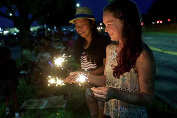 Elizabeth Garten, 12, of Newtown, and Allison Yap, 12, of Brookfield, hold  sparklers while they wait for the fireworks at the Danbury Fair Mall to start, on Thursday night, July 2 2015, in Danbury, Conn.