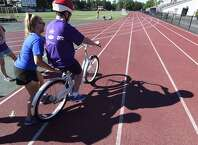 """Children with disabilities learned how to ride bicycles at Union College on Friday. It was part of a program run by Stride Adaptive Sports this week that helped 40 children  learn to ride two-wheel bikes. """"I Can Ride"""" Bike Camp, held at the Achilles Rink and the college's outdoor track, was financed through a $10,000 grant from the Schenectady Foundation. The Autism Society also partnered with Stride. (Skip Dickstein / Times Union)"""