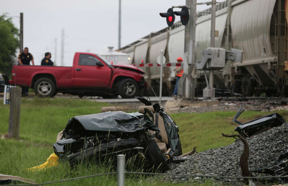 Police and railroad officials monitor the scene of an accident Friday July 3, 2015 on Basse Road and the Union Pacific railroad tracks. Police spokesman Douglas Greene said a red pickup truck and a car collided head-on about 6:00 a.m. and then a northbound freight train approched and hit the car. Two people in the truck were not seriously injured and the driver of the car was transported to University Hospital in serious condition. Photo: John Davenport, San Antonio Express-News / ©San Antonio Express-News/John Davenport