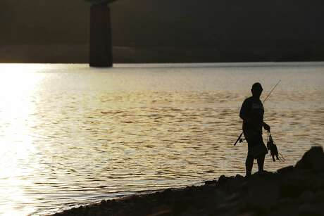 Danny Keen of Big Bend, CA, carries freshly caught bass beside Lake Shasta on Wednesday, July 1, 2015. Mercury levels in bass and catfish in Lake Shasta may be higher than reported in state fishing guidelines, posing a threat to human health. Photo: Terray Sylvester, The Chronicle