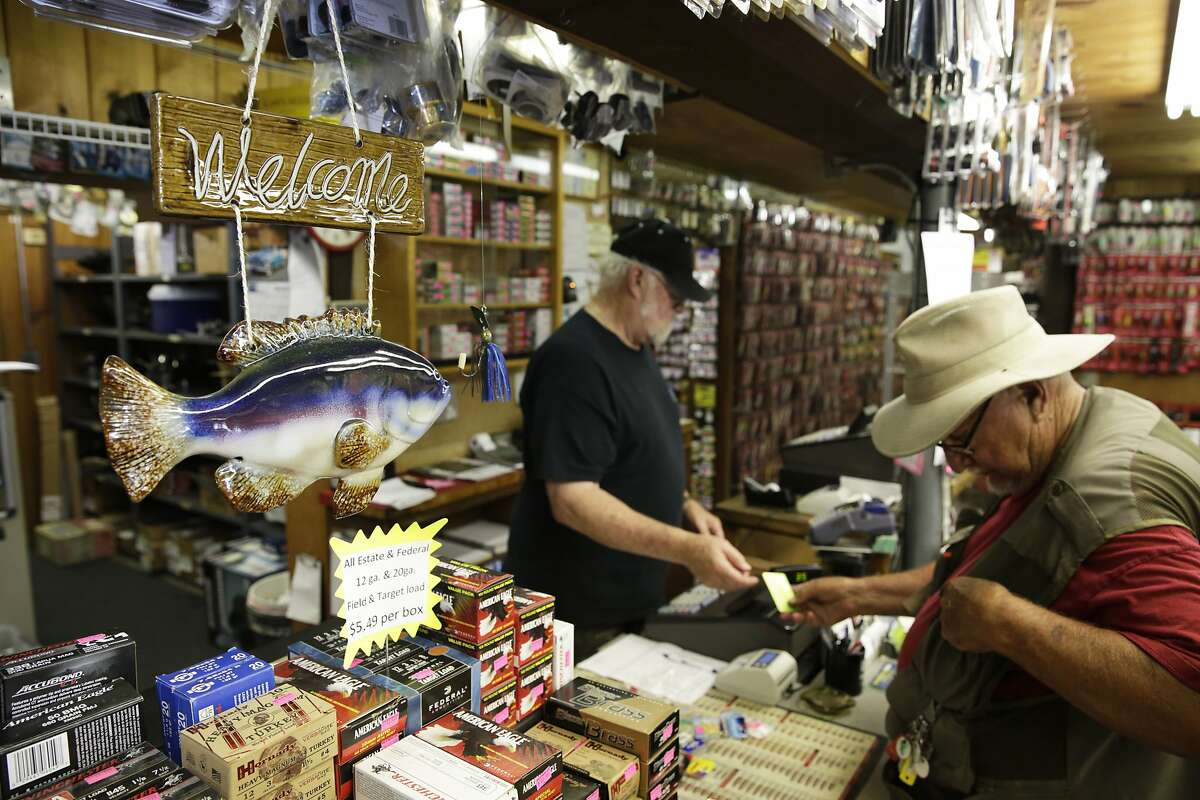 Larry Baker, an employee at Phil's Propellers, makes a sale in the fishing and tackle store in Shasta Lake, CA, on Wednesday, July 1, 2015. Mercury levels in bass and catfish in nearby Lake Shasta may be higher than reported in state fishing guidelines, posing a threat to human health.
