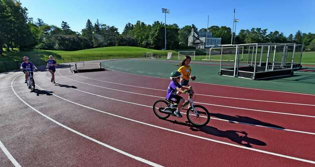 Biking students move around the track with their volunteers during the I Can Ride Bike Camp at Union College Friday morning July 3, 2015 in Schenectady, N.Y.  The I Can Ride Bike Camp is designed to take special needs youths and teach them to ride bikes.   (Skip Dickstein/Times Union) Photo: SKIP DICKSTEIN / 00032483A