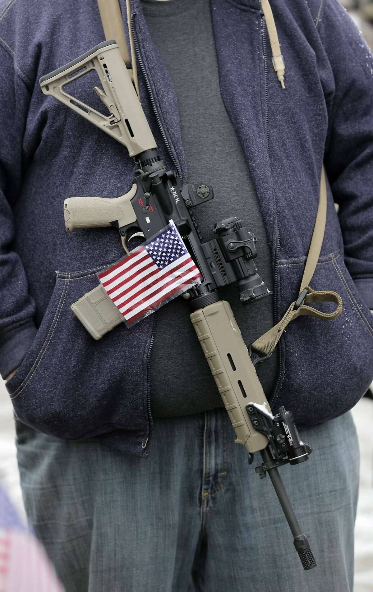 FILE - In this Saturday, Feb. 23, 2013 file photo, a gun-rights activist carries his rifle decorated with a U.S. flag during a