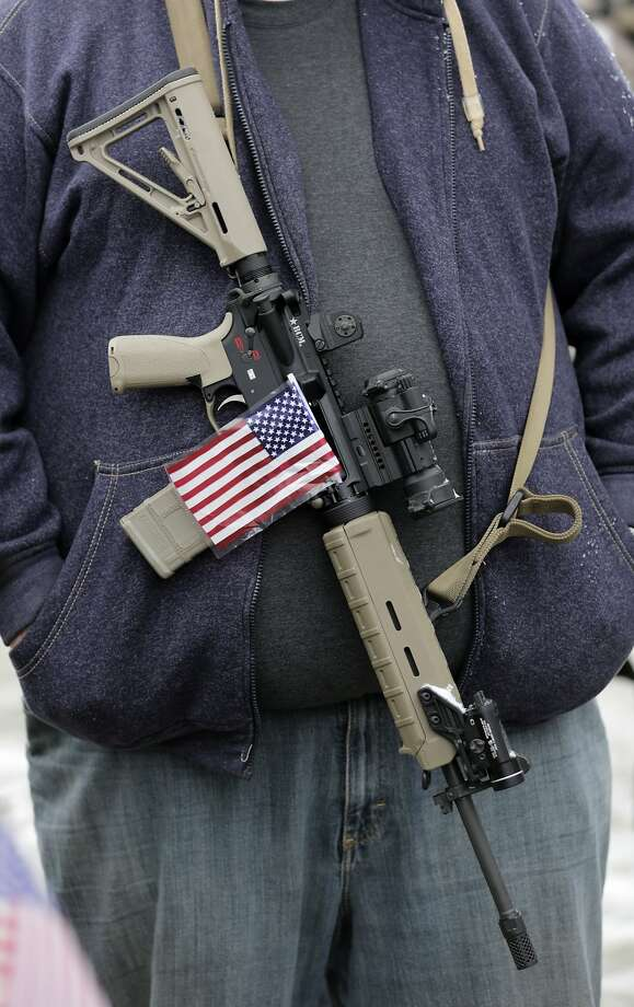 """FILE - In this Saturday, Feb. 23, 2013 file photo, a gun-rights activist carries his rifle decorated with a U.S. flag during a """"National Day of Resistance"""" rally at the Utah State Capitol in Salt Lake City, Utah. Activists said they were were there to show their support for the U.S. Constitution and the 2nd Amendment. (AP Photo/Rick Bowmer) Photo: Rick Bowmer, Associated Press"""