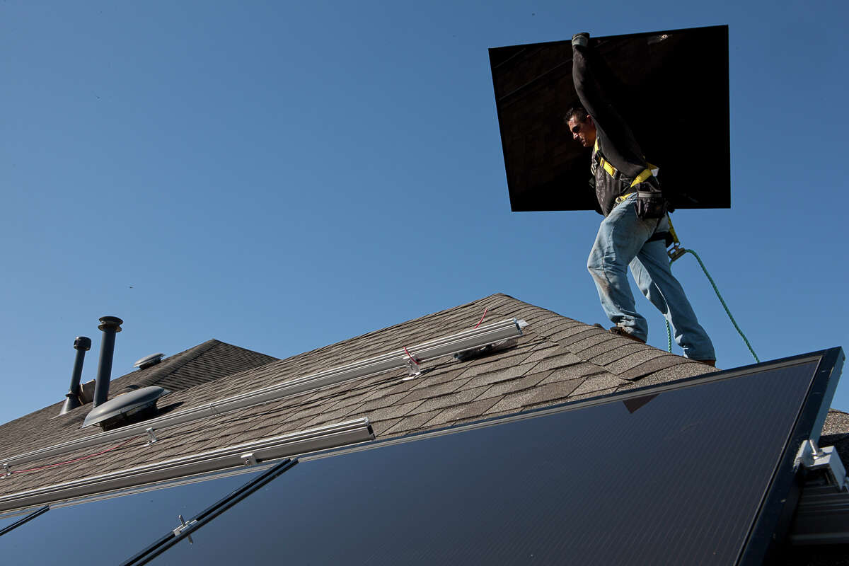 A worker with a solar installation company prepares to install a rooftop system. CPS Energy will achieve its goal of 20 percent generation from renewable sources in 2016, four years ahead of schedule.