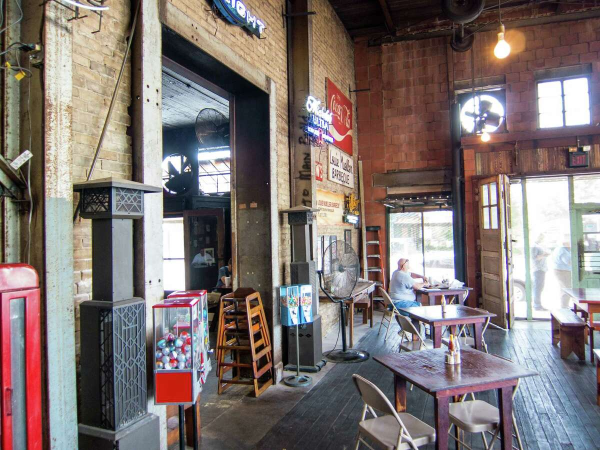 The dining room at Louie Mueller Barbecue in Taylor, above. Wayne Mueller cooks barbecue for students in Okinawa, Japan, left.