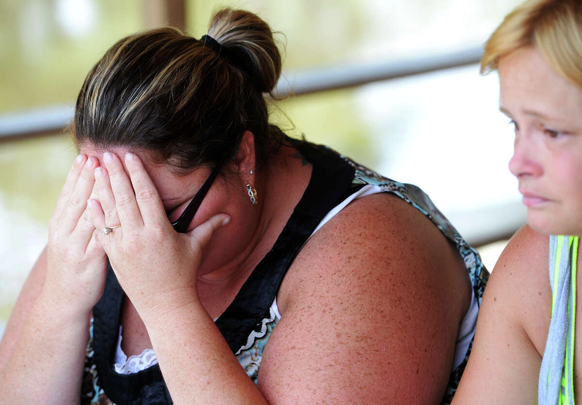 Angela Hoffpauir covers her face as she and Michelle Wright, right, recount the death of Tommie Woodward early Friday morning. Woodward, 28, was attacked and killed by an alligator while swimming in Adams Bayou at Burkart's Marina early Friday morning. The incident was the first fatal attack by an alligator in Texas in about 200 years. Photo taken Friday 7/3/15 Jake Daniels/The Enterprise